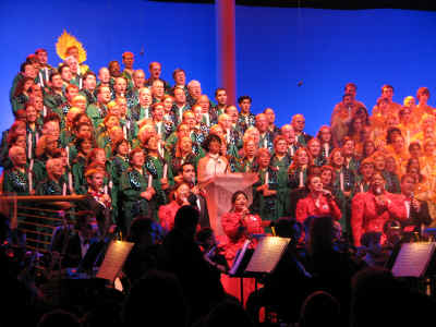 Disney Cast volunters in green robes make up the Christmas tree and the Voices of Liberty are in front in red and black